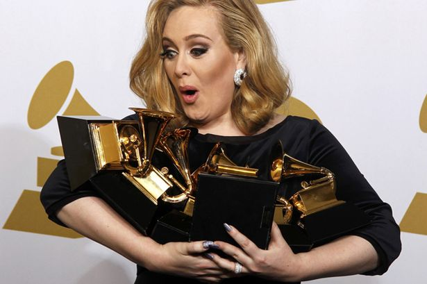 Singer Adele holds all six of her Grammys she scooped at the 54th Grammy Awards
